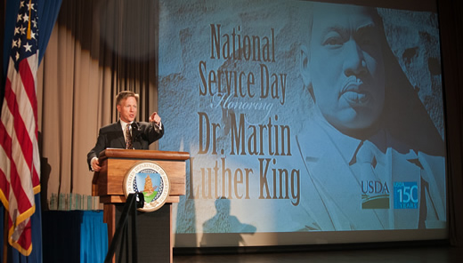 Max Finberg, Director, Faith Based and Neighborhood Partnerships, Master of Ceremonies reads a children's book of Dr. Martin Luther King's life to the audience during the National Service Day and Martin Luther King Celebration.